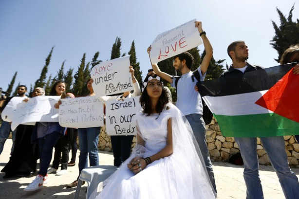 An Israeli Arab young woman wears a bridal gown as she plays the part of a bride without her groom as they pass the Rose Garden on their way to the Jerusalem offices of Israeli Prime Minister Benjamin Netanyahu